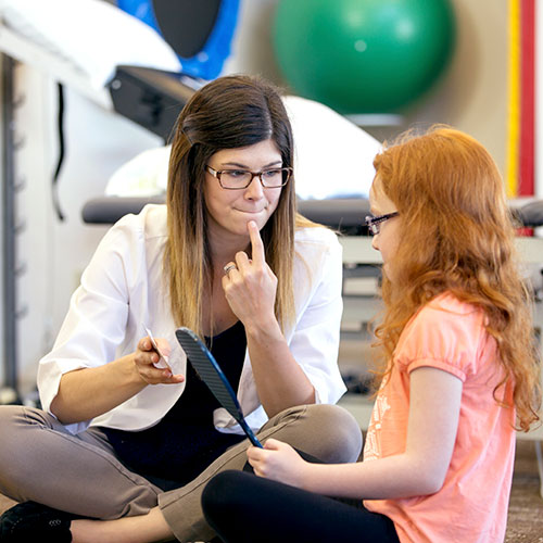 speech language pathology professional working with child